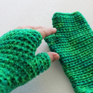 Inside Out Mitts Crochet Pattern by ReVe Design Co - in green - one hand on model reaching for other glove