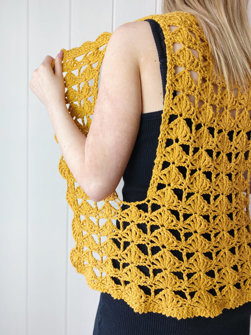 Fantail Vest Crochet Pattern by ReVe Design Co - Mustard cotton - modeled - from side - model holding front panel out