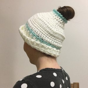 Early Morning Hair Hat Crochet Pattern by ReVe Design Co - from back on model - brim half turned up - in white with teal accents 2
