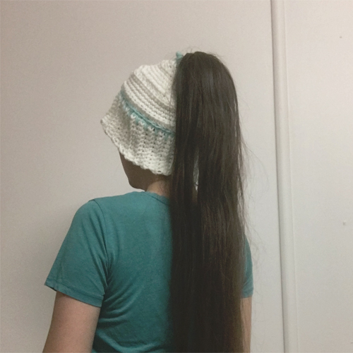 Early Morning Hair Hat Crochet Pattern by ReVe Design Co - from back on very long haired model - brim turned down - in white with teal accents 2