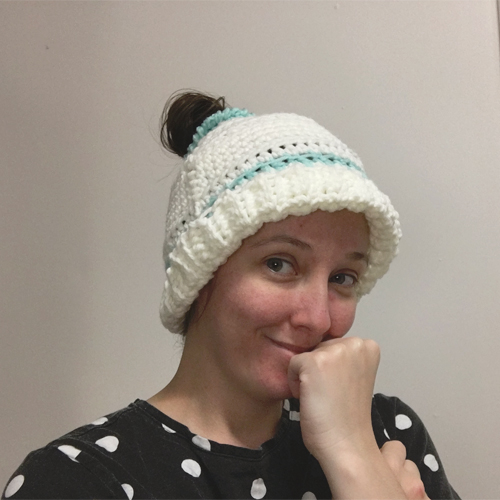Early Morning Hair Hat Crochet Pattern by ReVe Design Co - from front on model - cuff turned up - in white with teal accents