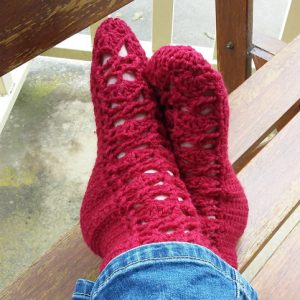 Pretty Feet Socks Crochet Pattern - on model in jeans - feet crossed at ankle on outdoor chair