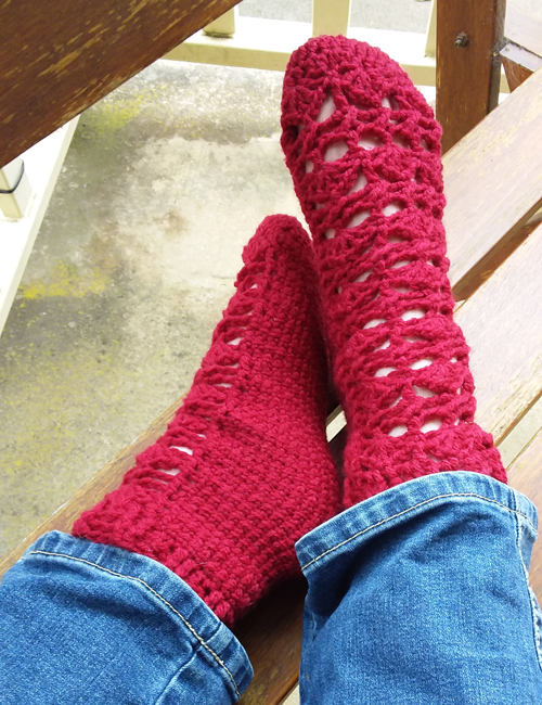 Pretty Feet Socks Crochet Pattern - on model in jeans - one foot on side against other foot with heel touching ankle on outdoor chair