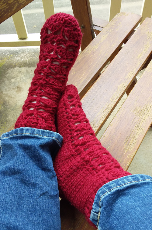 Pretty Feet Socks Crochet Pattern - on model in jeans - right foot on side against left foot with heel touching ankle on outdoor chair